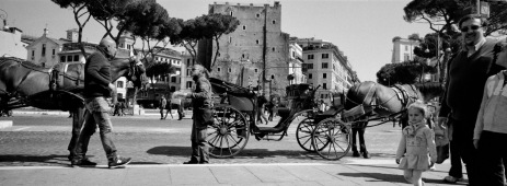 Two men talking during a break from work, leaving their horse-drawn carriages next to the sidewalk, while some tourists walk by near the Imperial Forum. Rome, Italy 2016. © Matteo Bastianelli