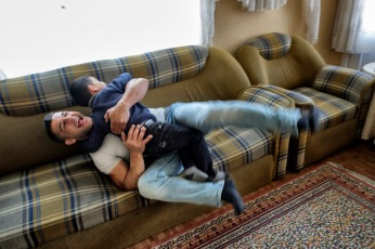 39-year-old award-winning Syrian bodybuilder, Ibrahim Shehabi, plays with his 6-year-old son Radwan on the couch. They both have been sheltering in Turkey for two years now. Istanbul, Turkey 2016. © Matteo Bastianelli