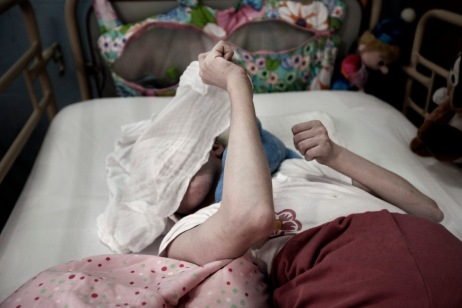 A girl plays hide-and-seek in her bed, laughing behind a bib left to her by a nurse at a meal-time. Gornja Bistra, Croatia 2009. © Matteo Bastianelli