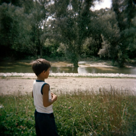 A child watches a river through vegetation and the path which leads to a Rom camp-site in Podturen, in the region of Medimurje. Podturen (Međimurje), Croatia 2009. © Matteo Bastianelli