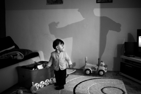 Alen Smajić, 1-year-old, listening music on TV while his father Adis is dancing in front of him. Sarajevo, Bosnia and Herzegovina, 2014. © Matteo Bastianelli