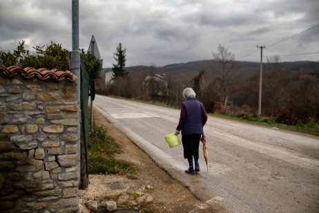 """A woman walks along the edge of a road in the vicinity of the city center, destroyed by the earthquake that took place on August 24. Amatrice, Italy 2016. © Matteo Bastianelli for """"La Stampa"""""""