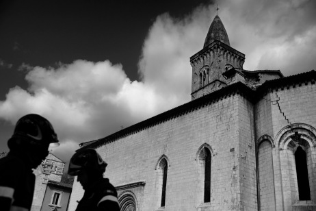 """Two firefighters are seen in front of the collegial church of Santa Maria, badly damaged by the earthquake. Visso, Italy 2016. © Matteo Bastianelli for """"La Stampa"""""""