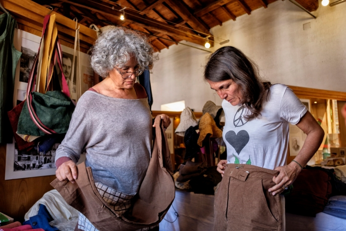 Rachele Invernizzi, owner of the first hemp processing center in southern Italy, choosing a pair of pants at a stall selling hemp fabric clothes. Canepina (Viterbo), Italy 2016. © Matteo Bastianelli