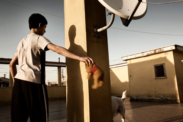 """Marco, Nadia's son, playing with a dog on the terrace at """"Casale de Merode"""". Rome, Italy 2009. © Matteo Bastianelli"""