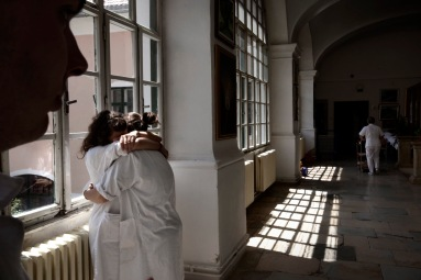 After a difficult day, in which patients have suffered epileptic fits and breathing difficulties, two volunteers exchange a friendly hug while a nurse takes meals into a room. Gornja Bistra, Croatia 2009. © Matteo Bastianelli