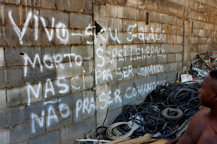 """A guy walks through the favela of Jardim Gramacho, controlled by the Red Command (Comando Vermelho). The writing on the wall says: """"Alive - I'm criticized, dead - I will be remembered, born to be the command, not to be commanded."""" Rio de Janeiro, Brazil 2015. © Matteo Bastianelli"""