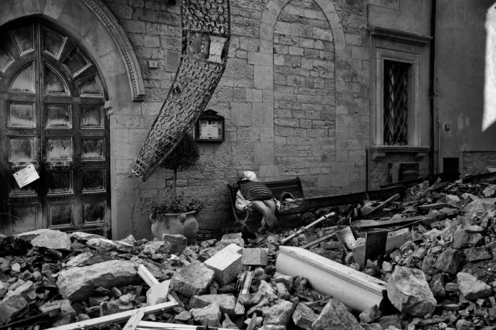 """A scarecrow surrounded by rubble in front of the Priori Palace in Visso, now the city hall. Visso, Italy 2016. © Matteo Bastianelli for """"La Stampa"""""""