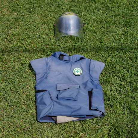 A flak jacket and a visored helmet on the ground. This is the uniform of deminers. Brčko, Brčko District, Bosnia and Herzegovina, 2014.