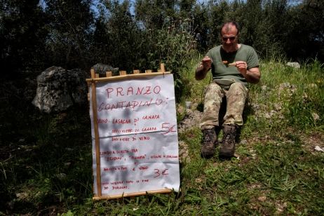 "A man is about to enjoy his lunch. In the foreground the ""peasant menu"" based on hemp and served during the hemp seed planting party. Castiglione d'Otranto, Italy 2016. © Matteo Bastianelli"