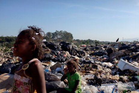 Two little girls in the site of one of the largest dump in the world, Jardim Gramacho, closed in 2012 after being in operation for 34 years, and then turned into a favela. On the background a flow of vultures are seen eating garbage. Rio de Janeiro, Brazil 2015. © Matteo Bastianelli
