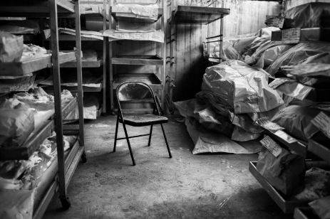 A chair between the human remains and personal items in the morgue of the Krajina Identification Project. Family members of the victims come to talk with the ICMP staff, and can see for the last time their loved ones. Sanski Most, Bosnia and Herzegovina, 2014. © Matteo Bastianelli