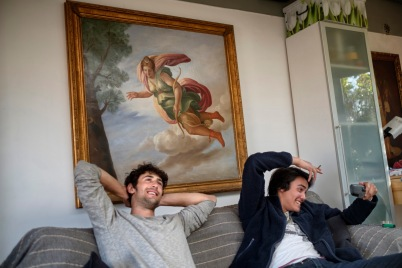 Two young men are seen seated on the couch, at home, smoking a joint. Rome, Italy 2017. © Matteo Bastianelli