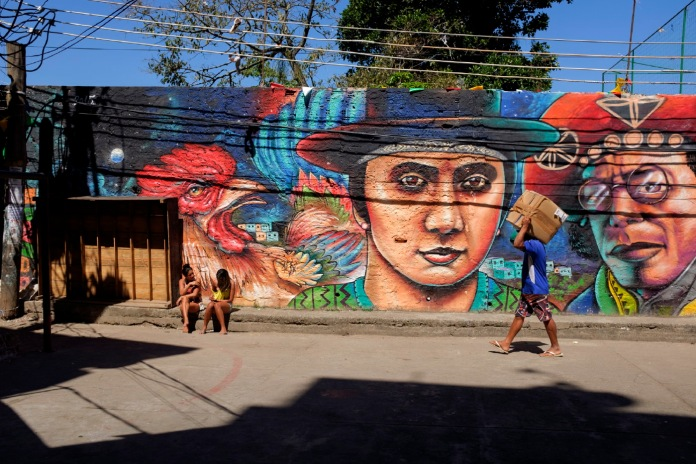 A man carries a package while two girls sit in front of a mural in the favela of Cantagalo-Pavão-Pavãozinho, in the south of Rio de Janeiro, Brazil 2015. © Matteo Bastianelli