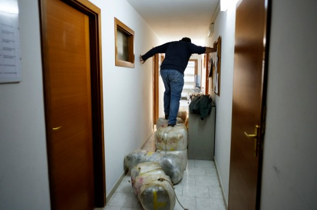A member of the Counter-narcotics Group (G.O.A.) in the tax unit of the Lecce financial police goes down the hall of the barracks walking on some bags containing marijuana seized in a counter-narcotics operation. Lecce, Italy 2016. © Matteo Bastianelli