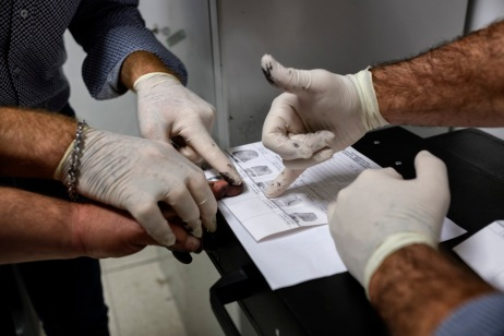 Two members of the Counter-narcotics Group (G.O.A.) in the tax unit of the Lecce financial police are seen taking the fingerprints of 49-year-old L.G., arrested for driving a van containing about 330 kilos of marijuana coming from Albania. Lecce, Italy 2016. © Matteo Bastianelli