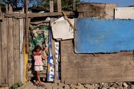 A little girl in front of a shack in the site of the former dump of Jardim Gramacho, closed in 2012 after being in operation for 34 years and then turned into a favela. Rio de Janeiro, Brazil 2015. © Matteo Bastianelli