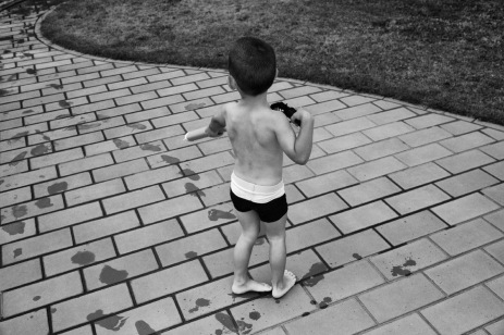 3-year-old Alen Smajic, is seen playing with a water gun by the pool. Velletri, Italy 2016. © Matteo Bastianelli