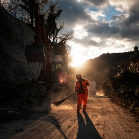 Men work with a backhoe to remove rubble and debris. The earthquake triggered landslides and rockfalls on roads. Triponzo, Italy 2016. © Matteo Bastianelli