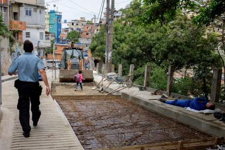 A policeman is seen walking while a little girl comes home from school and a worker rests on the street in the favela of Cantagalo. Rio de Janeiro, Brazil 2015. © Matteo Bastianelli