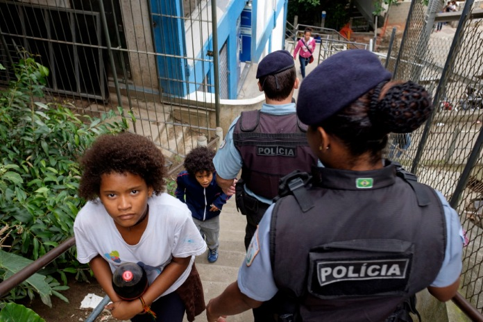 Two UPP policemen (Pacifying Police Unit) monitor the situation in the favela of Cantagalo while two children come home. Rio de Janeiro, Brazil 2015. © Matteo Bastianelli