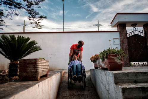 36-year-old Alberico Nobile, who was left quadriplegic after a car accident, is seen going out for a stroll accompanied by his friend Vincenzo. Talsano (Taranto), Italy 2016. © Matteo Bastianelli