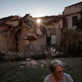 70-year-old Maria Pia Cortelli in the garage of her house. On the background, her neighbor's house destroyed by the earthquake. Norcia, Italy 2016. © Matteo Bastianelli