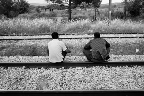 Two asylum seekers take a rest on the railway tracks in the buffer zone between Greece and FYROM. Idomeni, Greece 2015. © Matteo Bastianelli