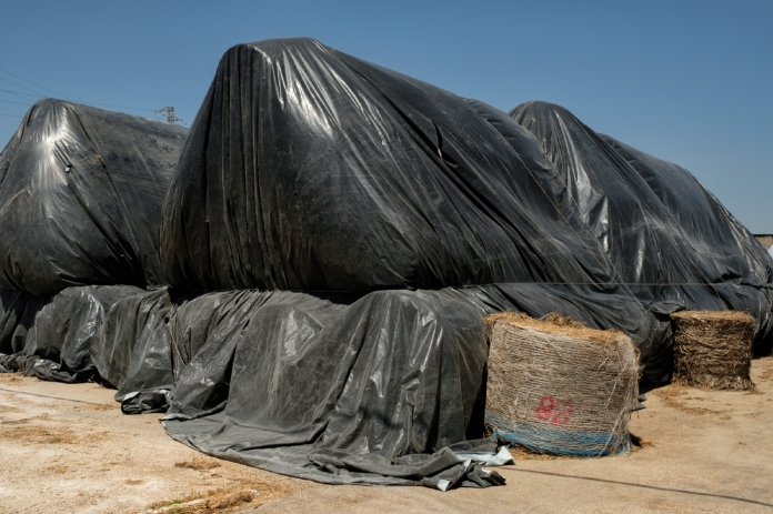 Hemp straw bales covered and stored in the warehouse of an industrial hemp processing center. Crispiano (Taranto), Italy 2016. © Matteo Bastianelli