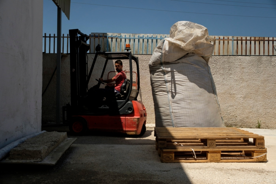 A worker drives a forklift truck to transport hemp processing residues that are used to produce pellets. Crispiano (Taranto), Italy 2016. © Matteo Bastianelli