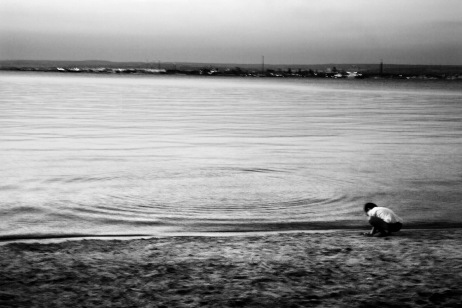 A child play on the sand in front of the Big Sea. Taranto, Italy 2013. © Matteo Bastianelli