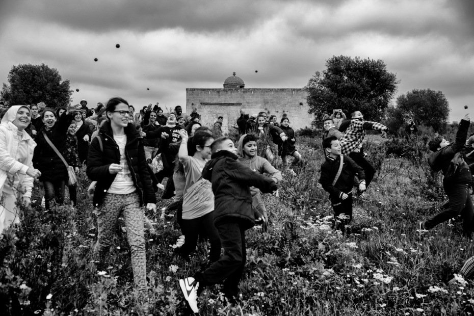 Some school children from the city of Taranto are seen with priests and nuns tossing balls of clay, soil and hemp seeds to start the sowing at the Fornaro brothers' farmhouse. Taranto, Italy 2016. © Matteo Bastianelli
