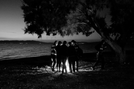 A group of Syrian refugees just arrived from the coastal town of Dikili, Turkey, gather around a fire on the shore to warm themselves before sunrise. Each one of them have had to pay 1 thousand dollars in order to cross the Aegean Sea and reach the Greek coast. Mytilene, Lesbos, Greece 2015. © Matteo Bastianelli