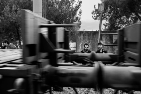 Some refugees are seen behind a train heading to Gevgeljia. Many of them have died on this route after being hit by trains. Idomeni, Greece 2015. © Matteo Bastianelli