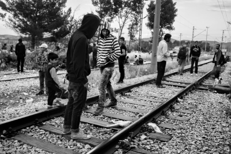 Some asylum seekers looking at a dog just hit by a train. Many people have died in the same way, walking along the railway tracks to reach FYROM. Idomeni, Greece 2015. © Matteo Bastianelli