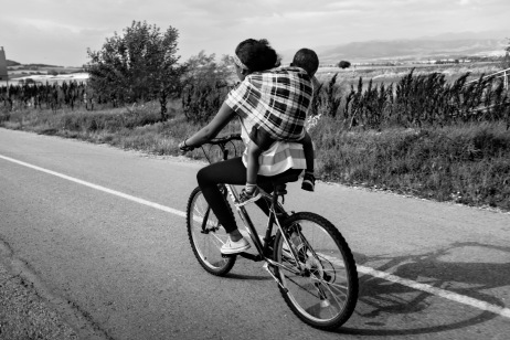 An Eritrean asylum seeker with her son on a bicycle on their way to the Greek-FYROM border. Evzoni, Greece 2015. © Matteo Bastianelli