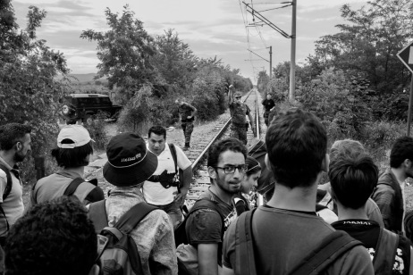 A group of refugees tries to cross the Greek-FYROM border walking along the railway tracks while a FYROM border policeman orders them to go back to Greece. FYROM 2015. © Matteo Bastianelli
