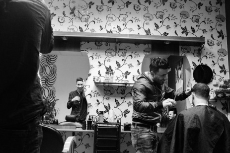 23-year-old Syrian refugee Mohamad Al Masalmeh stares at himself in the mirror, while his 24-year-old cousin Hani is having his haircut at a Syrian-Kurdish barber in the area and their friend, Hassan, enjoys the scene. Soest, Germany 2016. © Matteo Bastianelli