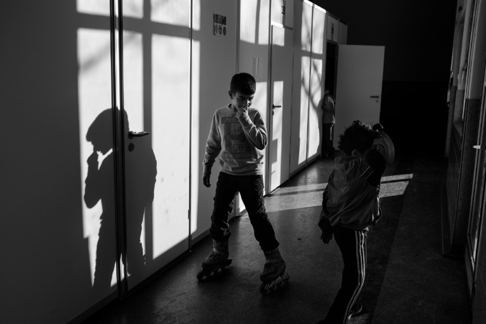 A Kurdish kid skates in a former sports centre turned into a refugee camp while others of his own age walk along the corridor. Sichtigvor, Germany 2016. © Matteo Bastianelli