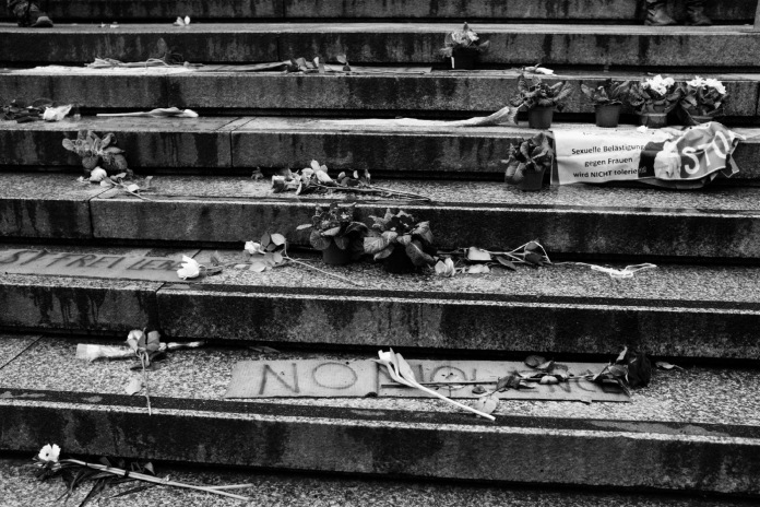Roses, more flowers and signs against gender-based violence left by a group of refugees on the steps of the Cathedral in Cologne. Cologne, Germany 2016. © Matteo Bastianelli