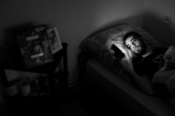 24-year-old Syrian refugee Hani Al Masalmeh looking at his phone during the night. Hani usually suffers from insomnia and bad dreams. A few months earlier he had found pictures of his brother's corpse on a social network, after forces loyal to Bashar Al-Assad had bombed his home in Syria on 17 September 2015. Belecke (Warstein), Germany 2016. © Matteo Bastianelli