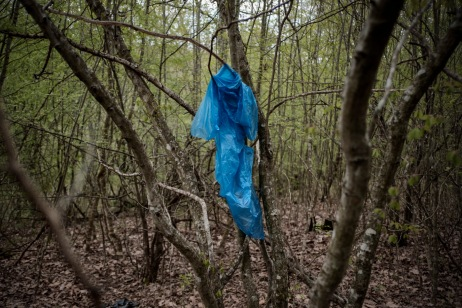 """A raincoat hanging from a tree branch. In the forests between Bulgaria and Turkey, there are a large number of personal belongings and clothes left behind by border crossers. Volunteers from the """"Vasil Levski"""" Bulgarian Military Veterans Union believe illegal crossings are the work of soldiers and terrorists, not of migrants. Yasna Polyana, Bulgaria 2017. © Matteo Bastianelli"""