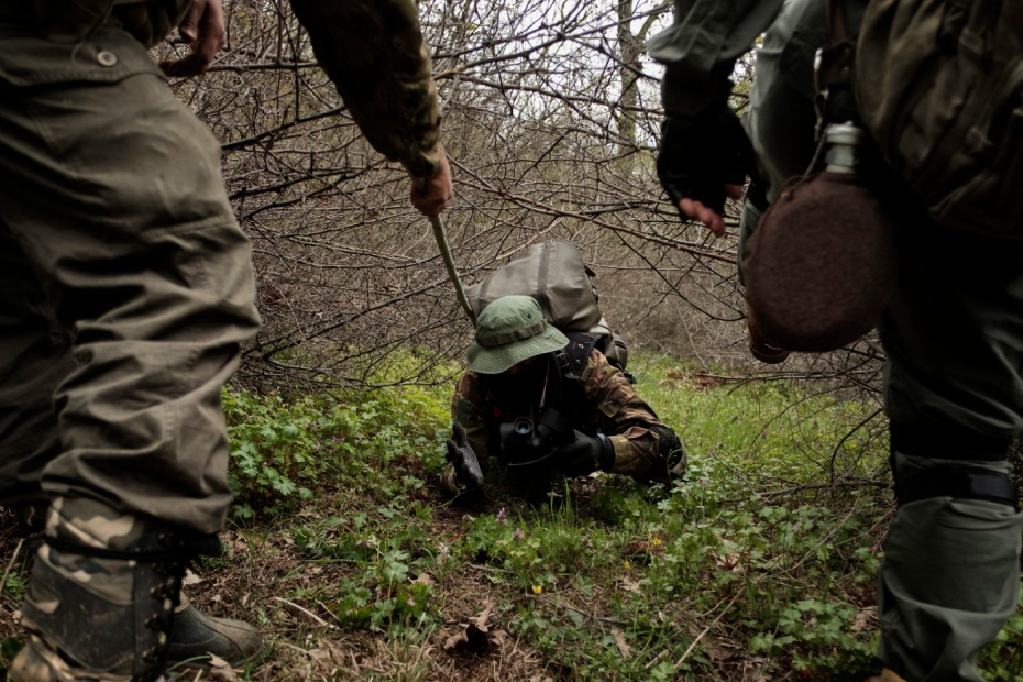 """A 31-year-old man originally from Burgas, is seen crawling under the brambles whilst patrolling the border. «I decided to join the """"Vasil Levski"""" Bulgarian Military Veterans Union -he affirms- because our government doesn't want to protect us. Nobody will defend us, and therefore, we take it unto ourselves. This is a planned invasion. Those who illegally cross the border are soldiers, not just migrants». Yasna Polyana, Bulgaria 2017. © Matteo Bastianelli"""