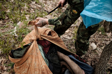 """A volunteer from the """"Vasil Levski"""" Bulgarian Military Veterans Union opens a bundle of clothing with a knife, after finding it on the side of a road, in the vicinity of a forest. Yasna Polyana, Bulgaria 2017. © Matteo Bastianelli"""