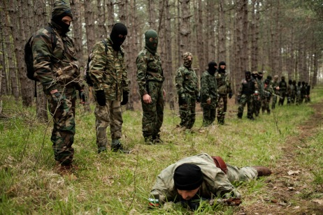 """60-year-old Vladimir Rusev, a retired military officer and Chief Commander of the """"Vasil Levski"""" Bulgarian Military Veterans Union, shows the volunteers how to crawl along the ground in the forest so as not to be seen by the """"enemies"""". Tsarevo, Nestinarka camp-site, Bulgaria 2017. © Matteo Bastianelli"""