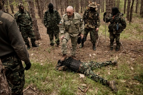 """60-year-old Vladimir Rusev, a retired military officer and Chief Commander of the """"Vasil Levski"""" Bulgarian Military Veterans Union, shows the volunteers how to pin a man to the ground. They don't want to be called migrant-hunters: they consider themselves the defenders of the European southern border. Tsarevo, Nestinarka camping, Bulgaria 2017. © Matteo Bastianelli"""