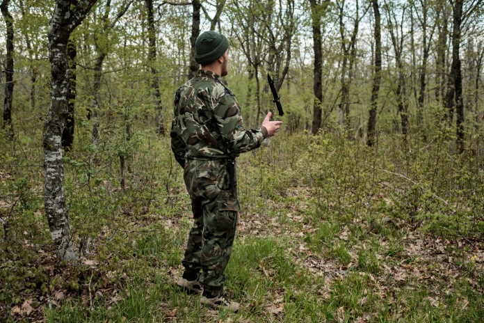 """A volunteer from the """"Vasil Levski"""" Bulgarian Military Veterans Union plays with a knife while surveilling the forest. Yasna Polyana, Bulgaria 2017. © Matteo Bastianelli"""