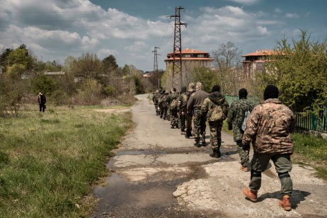 """Volunteers from the """"Vasil Levski"""" Bulgarian Military Veterans Union and from the """"BNO Shipka"""" are seen marching on their way back from the forest where they have been training, while a local resident observes them. Tsarevo, Bulgaria 2017. © Matteo Bastianelli"""