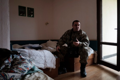 """A commander of the """"Vasil Levski"""" Bulgarian Military Veterans Union is seen in a room at a former fitness center turned into a base for volunteers, in the vicinity of the Nestinarka camp-site. Tsarevo, Bulgaria 2017. © Matteo Bastianelli"""
