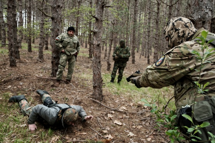 """The head instructor of the """"Vasil Levski"""" Bulgarian Military Veterans Union, who works as a lifeguard, points a gun at another volunteer during a drill simulating the capture of a man in the forest near Nestinarka camp-site. Tsarevo, Bulgaria 2017. © Matteo Bastianelli"""